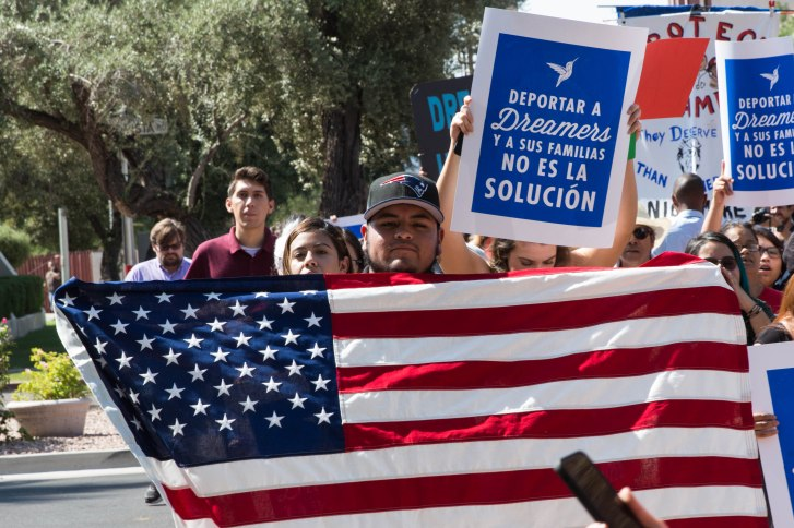 """""""I feel like I am a U.S. citizen. That's why I came wrapped in an American flag. This is my flag. This is my country,"""" Emmanuel Lopez Rafael, 19, of Mesa said at a protest following the end of the DACA program. (Photo by Tynin Fries/Cronkite News)"""