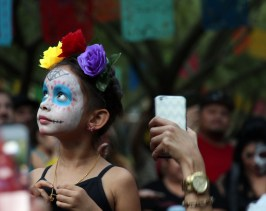 A child watches butterflies fly around her head as part of the Dia de los Muertos Festival at St. Mary's Basilica in Phoenix, Arizona on Nov. 6, 2016. (Photo by Tynin Fries)