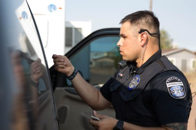 Officer Alejandro Barron of the Winslow police department collects fingerprints off a damaged car. (Photo by Tynin Fries/Cronkite News)