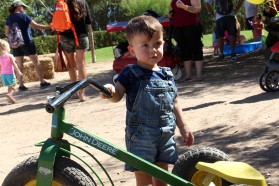 1-year old Kaden Noble plays with a John Deere tricylce at Schnepf Farm's Messy Fest on Sept. 17, 2016 in Queen Creek, Arizona. (Photo by Tynin Fries)