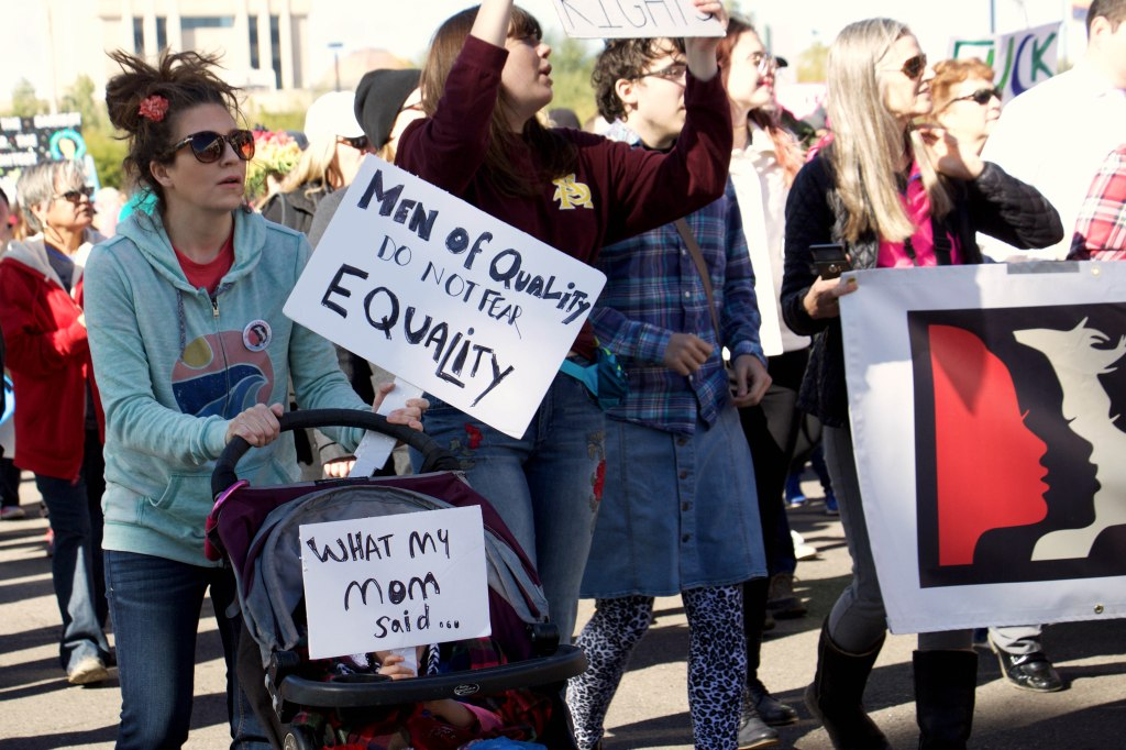 Rachel Xu, left, and her daughter Fiona Xu walk alongside hundreds of people at the Women's March in Phoenix, Arizona on Jan. 21. 2017. (Photo by Tynin Fries)
