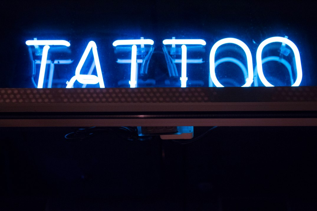 A neon sign outside of 27 Tatoo Studio lights up a dark window on Tuesday, Feb. 7, 2017. (Photo by Tynin Fries)